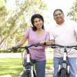 Senior Couple Riding Bikes In Park — ストック写真