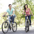 Stock Photo: Young Couple Riding Bike In Park