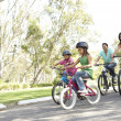 Young Family Riding Bikes In Park — Stock Photo