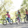 Foto Stock: Young Family Riding Bikes In Park