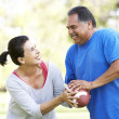 Senior Couple Exercising With American Football In Park — Stock Photo