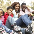 Stock Photo: Family Putting On In Line Skates In Park