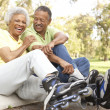 Senior Couple Putting On In Line Skates In Park — Stock Photo #4822708