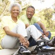 Senior Couple Putting On In Line Skates In Park - Stockfoto