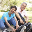 Stock Photo: Senior Couple Putting On In Line Skates In Park