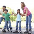 Family Putting On In Line Skates In Park — Stock fotografie