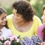 mujer Senior con hija adulta y tog jardinería nieta — Foto de Stock   #4822963