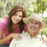 äldre man med vuxen dotter i trädgården — Stockfoto