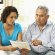 Senior Couple Studying Financial Document At Home — ストック写真