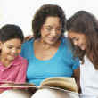 Stock Photo: Grandmother Reading With Grandchildren At Home Together