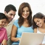 famille assis sur le canapé à la maison avec ordinateur portable — Photo