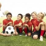 niños y niñas en el equipo de fútbol con el entrenador — Foto de Stock
