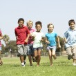Group Of Children Running In Park - Stock Photo