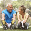 Senior Couple Exercising In Park - Stock fotografie