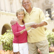 Senior Couple Walking Through City Street With Map — Stock Photo