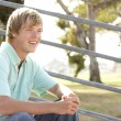 Teenage Boy Sitting In Playground - Stock Photo