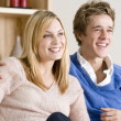 Young Couple Sitting On Sofa Together Watching TV — Stock Photo