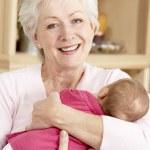Grandmother Cuddling Granddaughter At Home — Stock Photo