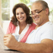 Stock Photo: Senior Couple Reading Newspaper At Home