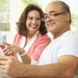 Senior Couple Reading Newspaper At Home - Foto de Stock  