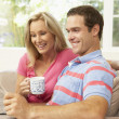 Foto Stock: Couple Reading Newspaper At Home