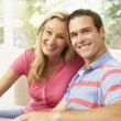 Young Couple Relaxing On Sofa At Home — Stock Photo #4823809