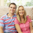 Young Couple Relaxing On Sofa At Home — Stock Photo #4823858