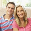 Young Couple Relaxing On Sofa At Home — Stock Photo