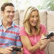 Young Couple Playing Computer Game On Sofa At Home — Stock Photo