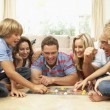 Family Playing Board Game At Home With Grandparents Watching — Stockfoto