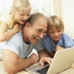Grandfather AndGrandchildren Using Laptop At Home — Stock Photo