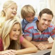 Foto Stock: Family Using Laptop At Home Together