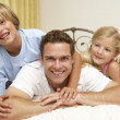 Father And Children Relaxing On Bed At Home - Stock fotografie