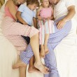Family Relaxing On Bed At Home - Stock fotografie