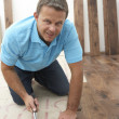 Builder Laying Wooden Flooring - Stock Photo