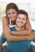 Young Man Giving Woman Piggyback Outdoors — Stock Photo