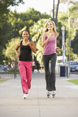 Two Female Friends Jogging On Street — Stock Photo