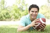 Retrato de hombre joven en el parque con el fútbol americano — Foto de Stock