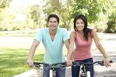 Jeune couple à vélo dans le parc — Photo