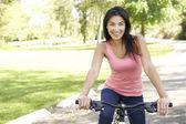 Genç kadın binicilik bisiklet park — Stok fotoğraf