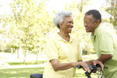 Senior Couple Riding Bikes In Park — Stockfoto