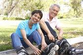 Senior Couple Putting On In Line Skates In Park — Stock Photo
