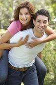 Giovane uomo dando all'aperto sulle spalle di donna — Foto Stock