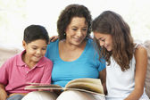 Grandmother Reading With Grandchildren At Home Together — Stock Photo