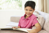 Young Boy Reading Book At Home — Stock Photo