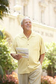 Senior Man Walking Through City Street With Map — Stock Photo