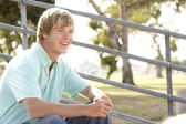 Teenage Boy Sitting In Playground — Stockfoto