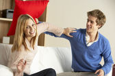 Young Couple Having Play Fight On Sofa — Stock Photo