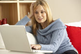 Young Woman Sitting On Sofa Using Laptop — Stock Photo