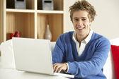 Giovane uomo usando il portatile a casa — Foto Stock